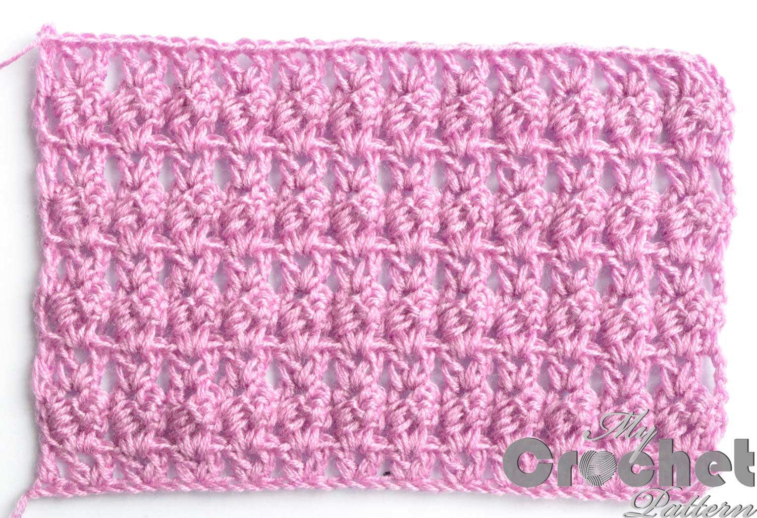 Photo of pink crochet openwork pattern with cluster and shell
